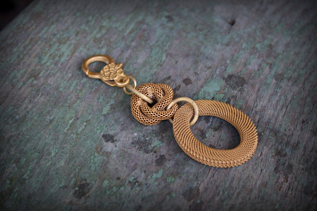 22 kt matte gold plated mesh elliptical pendant with love-knot.